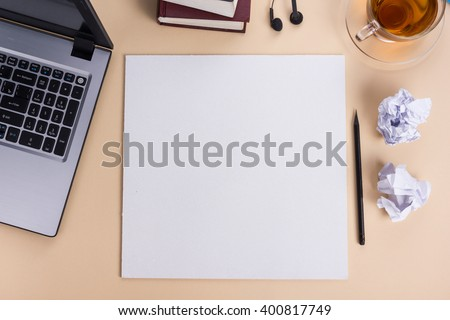 Office table desk with set of colorful supplies, white blank note pad, cup, pen, pc, crumpled paper, flower on beige background. Top view and copy space for text