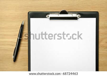 Office table with ball-pen and clipboard. - stock photo