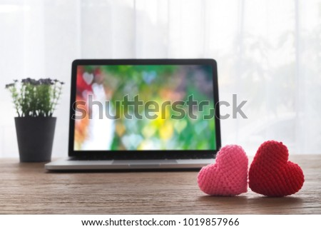 Office table with Beautiful couple knitted fabric heart shape, heart shape bokeh background on laptop screen and violet flower pot. view from front office table. valentine's day concept. #1019857966