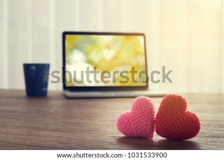 Office table with Beautiful couple knitted fabric heart shape, heart shape bokeh background on laptop screen and coffee cup. view from front office table.  concept of heart disease healthy care. #1031533900