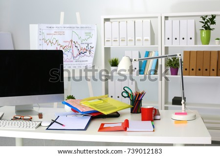 Office table with blank notepad and laptop - Shutterstock ID 739012183