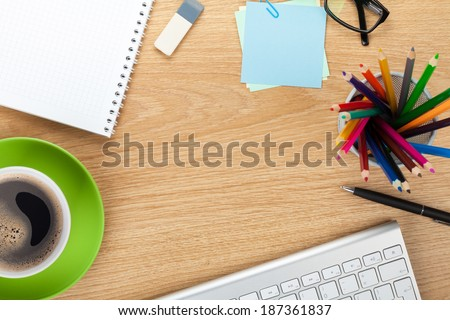 Office table with coffee cup, supplies and copy space