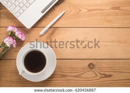 Office table with cup of coffee and flowers #620436887