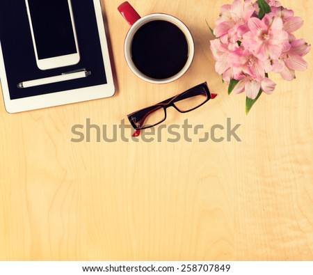 Office table with digital tablet, smartphone, reading glasses and cup of coffee. View from above with copy space