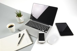 Office table with  laptop computer, notebook, digital tablet and smartphone on modern two tone (white and grey) background.
