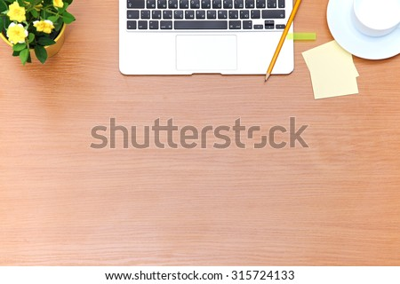 Office table with laptop, notepad and coffee cup. View from above with copy space