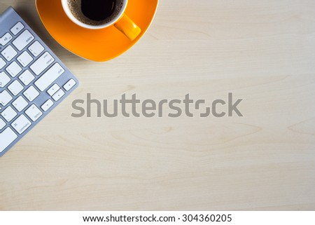 Office table with notepad, computer and coffee cup. View from above with copy space.