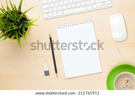 Office table with notepad, computer, coffee cup and flower. View from above with copy space