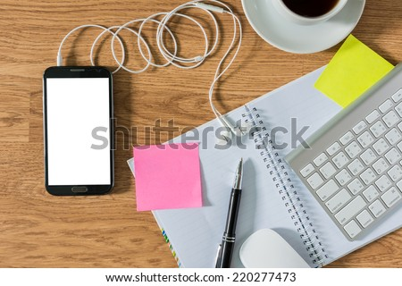 Office table with notepad, computer, coffee cup , computer mouse , pen , smartphone , headphone , sticky notes. View from above with copy space