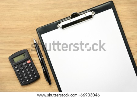 Office table with pen, calculator and empty paper for your text