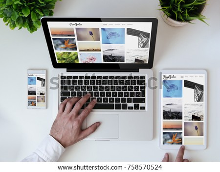 office tabletop with tablet, smartphone and laptop showing photo portfolio website