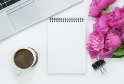 office theme, notepad for writing, cup of coffee and peony flowers at the white table background, copy space for text