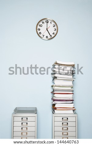 Office wall with clock stack of paperwork in outbox on file cabinet