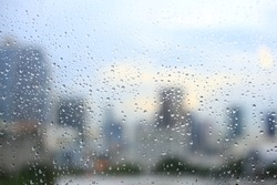 office window covered with rain water. water spray on window. after rain traffic, worker stuck in the office concepts. blur urban skyline background. rainy season concepts.
