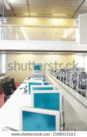 Office with multiple work stations on long desk