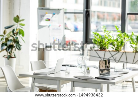 office with table, chairs, green plants and digital devices  #1494938432