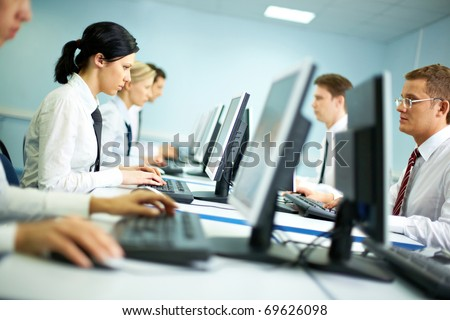 Office with white collar workers working on computers