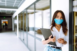 Office woman  worker  in sterile mask work in the office during an epidemic. COVID-19. Business concept.