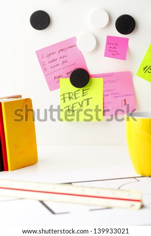Office work area. Desk with pink and yellow \'Post It\' notes.