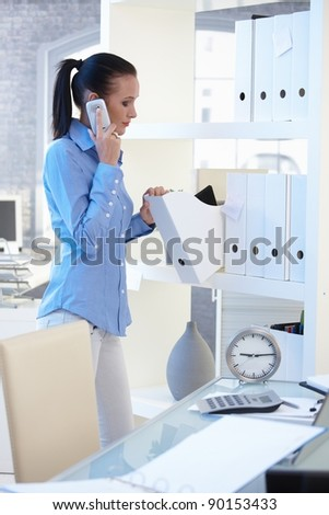 Office worker girl on mobile phone call standing at shelf, checking folders.?