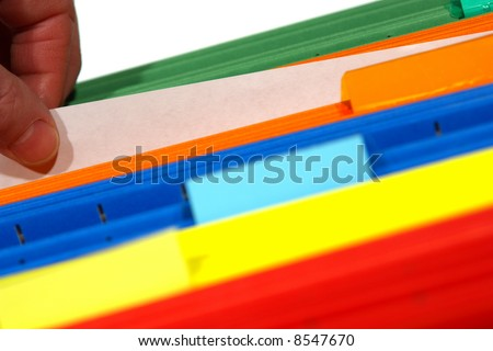 Office worker hand pulling out a blank sheet of paper from a stack of assorted colors file folders