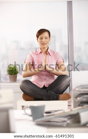 Office worker having a break, doing yoga meditation sitting in front of windows.?