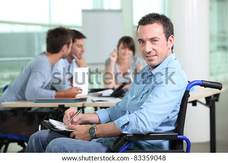 Office worker in a wheelchair with colleagues in the background
