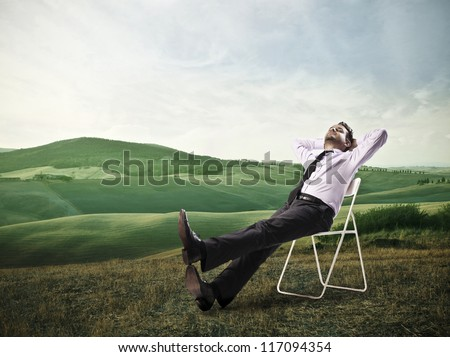 Office worker is lying on a chair in a large grace field