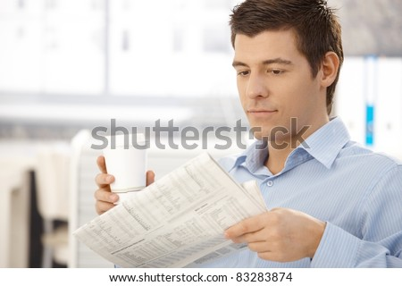 Office worker man on break reading papers, having takeaway coffee in office.?