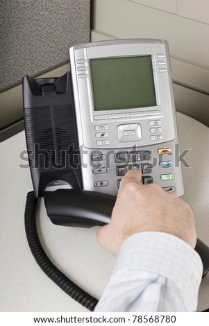 Office worker placing a call on an IP phone - stock photo