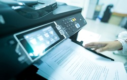 Office worker print paper on multifunction laser printer. Copy, print, scan, and fax machine in office. Modern print technology.  Photocopy machine. Document and paper work. Scanner. Secretary work.