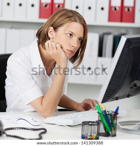 Office worker reading her computer monitor concentrating on the information while seated at her desk