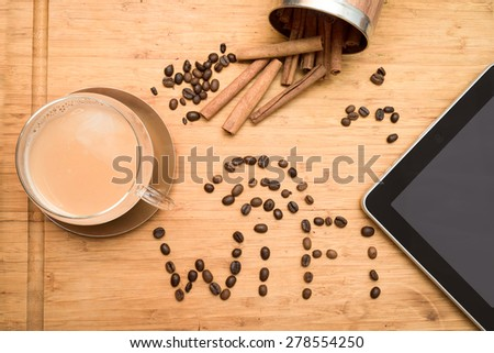 office worker\'s coffee break: composition of tablet, wi-fi world composed of coffee beans, cup of coffee with milk