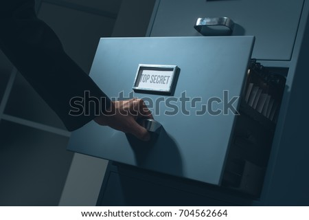 Office worker searching top secret confidential information in the office late at night, data theft and security concept Stock photo ©