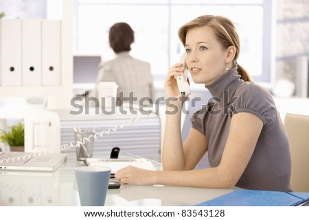 Office worker sitting at desk, talking on landline phone.?