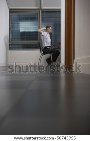 Office worker sitting with hands behind head in partly darkened office, side view