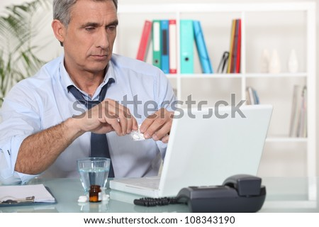 Office worker taking medication for headache