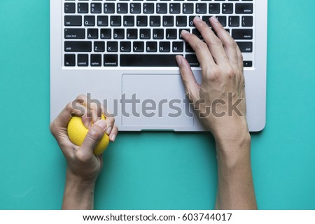 Office worker typing email on computer, feels stressed and nervous, holds a stress ball in her hand Сток-фото ©