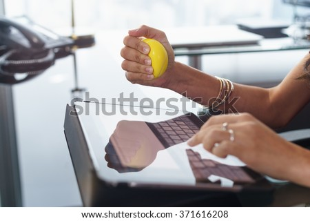 Office worker typing email on tablet computer. The woman feels stressed and nervous, holds an antistress yellow ball in her hand Сток-фото ©
