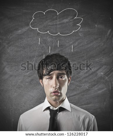 Office worker with a cloud drawn on a black board over him