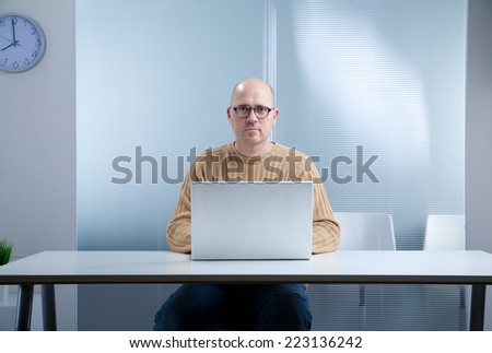 office worker with a nerd attitude and an open laptop on the top of an empty desktop in an almost empty room waiting for you to act