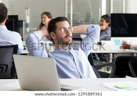 Office worker with closed eyes relaxing sitting at desk in coworking space cogitating holds hands behind head. Employee finished work resting planning dreaming about future goals stress relief concept