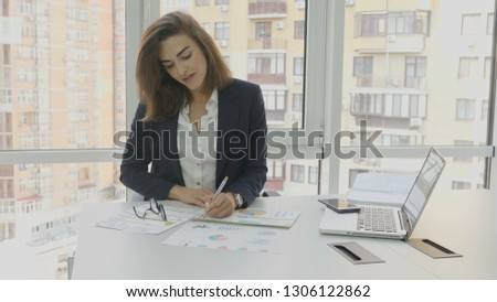 Photo of  Office workers, a business woman in glasses sits in an armchair in the office of an office building, develops studies documents made by her employees