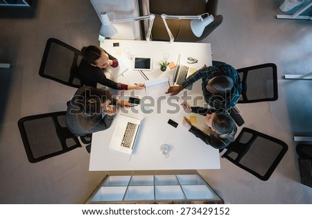 Office workers gather around a table to do research and implement new ideas. High angle view of multi-ethnic business people discussing in board room meeting