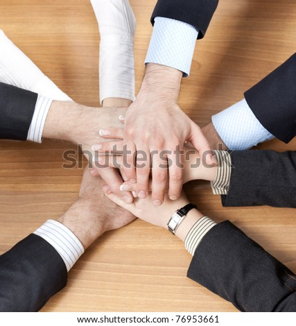stock-photo-office-workers-hold-hands-together-on-table-76953661.jpg