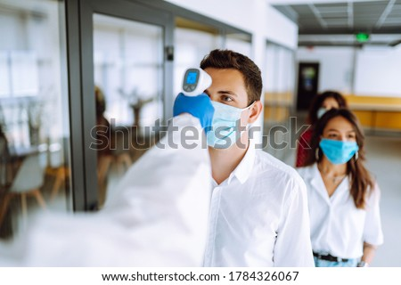 Office workers must go through fever measures using infrared digital thermometer check temperature measurement on the forehead during the coronavirus pandemic. Covid-19.