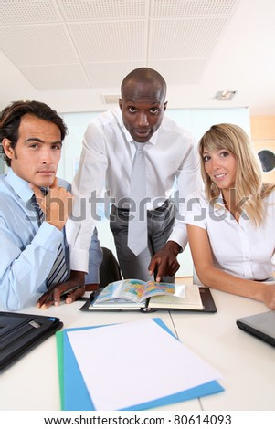 Office workers sitting around meeting table