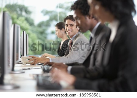 Office workers using computers, man reaching for telephone