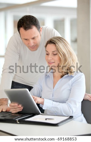 Office workers using electronic tab in the office