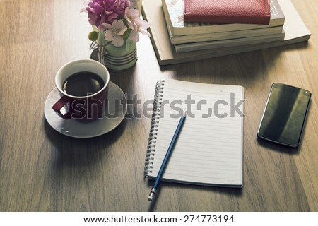 office working desk top view with book, smartphone, notepad and coffee cup - vintage style